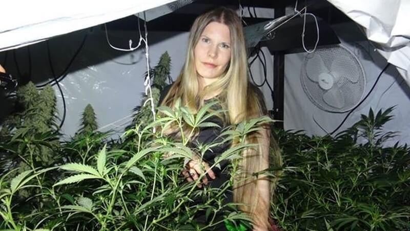 Cannabis Patientin zwischen Hanfpflanzen