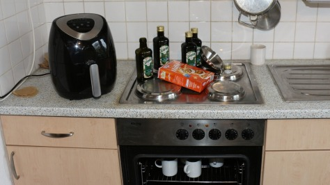 Tassen im Backofen, oben das Olivenöl, die Backmischung und der Trichter
