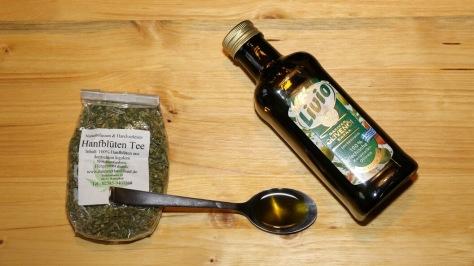 Hanfblütentee, Olivenöl und davor CBD Olivenöl auf einem Esslöffel