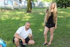 Ein Paar auf einer Wiese, der Mann inhaliert Marihuana
