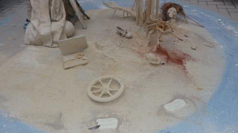 Straßenkunst mit Skelette auf Sand unter einer Giraffen