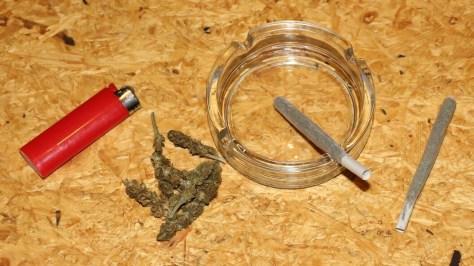 Ein Cannabis Joint im Aschenbecher, ein anderer daneben